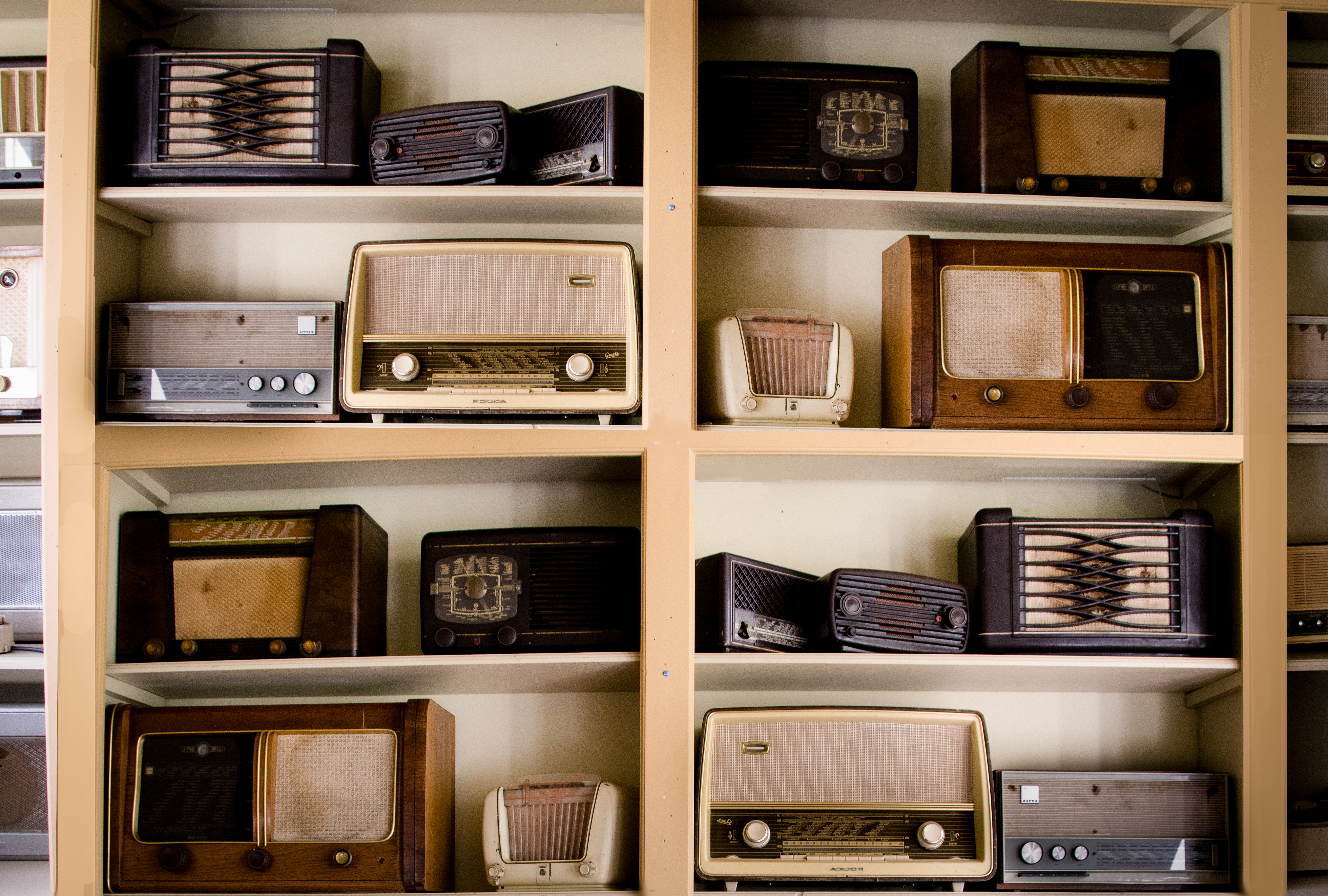 A photo of a shelving set with lots of old fashioned radios